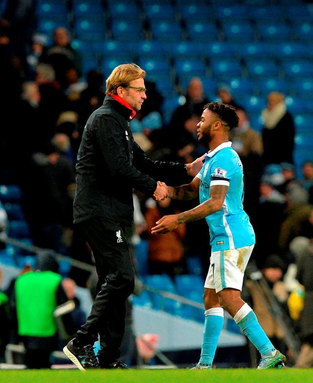 Liverpool manager Jurgen Klopp (left) shakes hands with Manchester City's Raheem Sterling