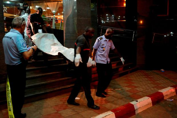 Nowhere is safe anymore: Malian officials carry a corpse down the stairs after the attacks on civilians at the Radisson Blu hotel in Bamako, Mali