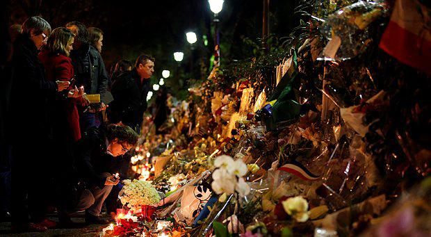 People lay flowers and candles as they gather at the memorial near the Bataclan