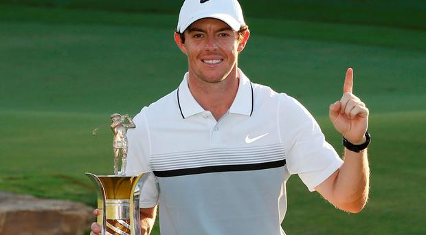 Rory McIlroy celebrates with the trophy after winning The Race to Dubai
