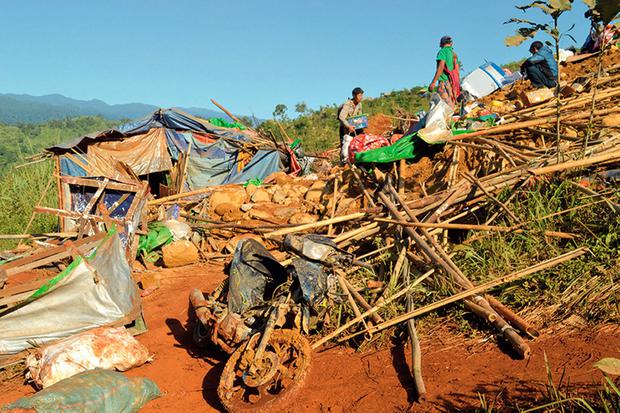 People look through their destroyed homes after a landslide at Phakant jade mine, Kachin State, Myanmar. (Eleven Media Group via AP)