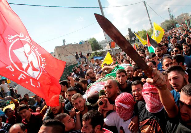 Palestinians carry the body of a man who was killed by Israeli security forces following attempted stabbing attacks, while others wave a knife and flags of the Popular Front for the Liberation of Palestine
