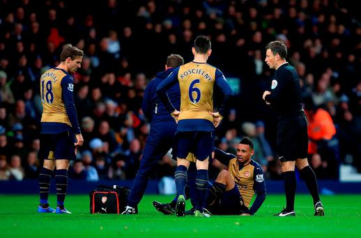 Arsenal's Francis Coquelin leaves the pitch with an injury as match referee Mark Clattenburg looks on during the Barclays Premier League match at The Hawthorns