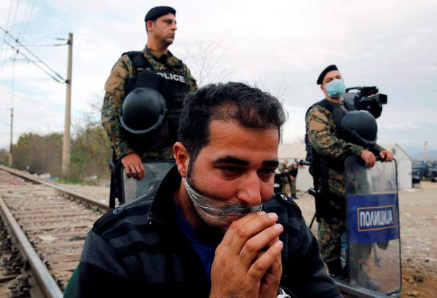 A stranded Iranian migrant has his lips shield as he sits on rail tucks at the borderline between Greece and Macedonia near the Greek village of Idomeni November 23, 2015. REUTERS/Yannis Behrakis
