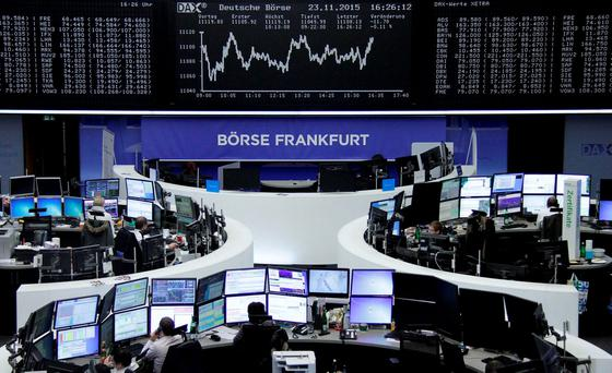 Traders are pictured at their desks in front of the DAX board at the stock exchange in Frankfurt. Photo: Reuters