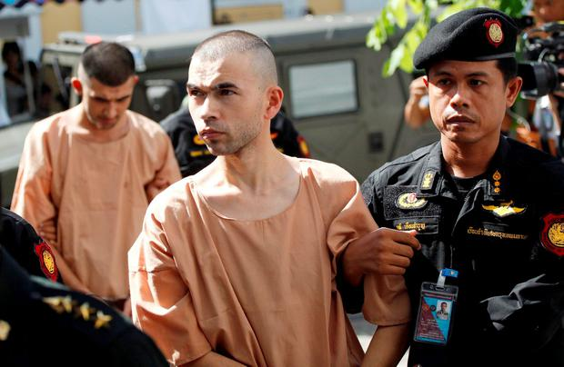 Police officers escort suspects in the Aug. 17 blast at Erawan Shrine, Bilal Mohammad, front, and Mieraili Yusufu, rear, as they arrive at a military court in Bangkok, Thailand