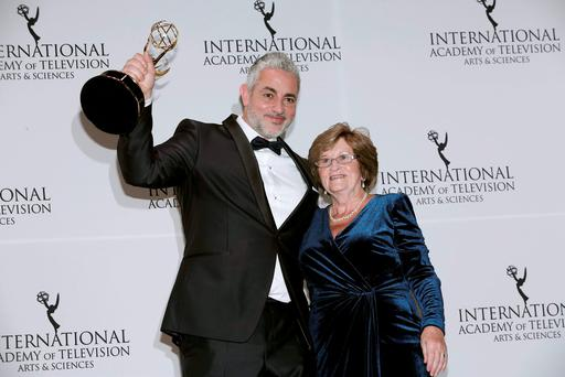 (L-R) Producer Baz Ashmawy and his mother Nancy Ashmawy pose with the International Emmy award in the 'Non-Scripted Entertainment' category