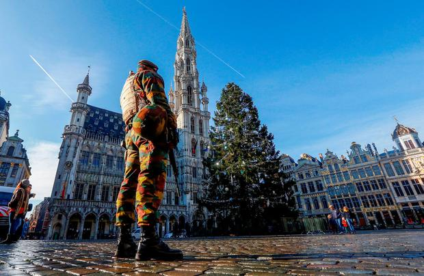 A Belgian soldier patrols in Brussels' Grand Place as police searched the area during a continued high level of security