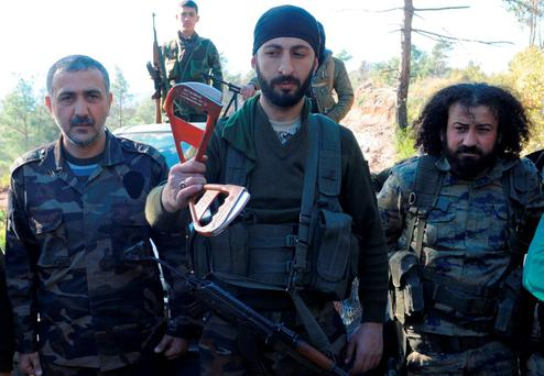 Alpaslan Celik, a deputy commander in a Syrian Turkmen brigade (centre), holds handles believed to be parts of a parachute of the downed Russian warplane near the northern Syrian village of Yamadi, near the Turkish-Syrian border, Syria. Reuters