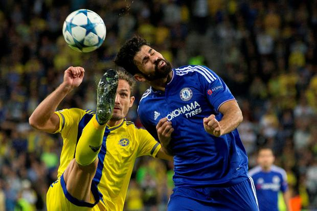 Maccabi Tel Avivs Carlos Garcia, left, clears the ball ahead of Chelseas Diego Costa during group G Champions League soccer in Haifa, Israel, Tuesday, Nov. 24, 2015. (AP Photo/Ariel Schalit)