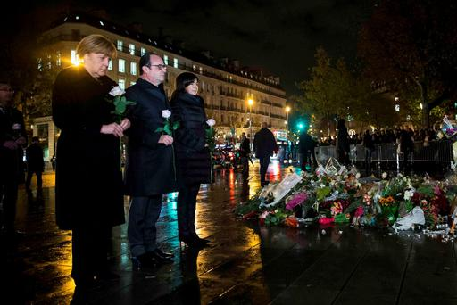 From L-R, German Chancellor Angela Merkel, French President Francois Hollande and Paris Mayor Anne Hidalgo each hold a white rose as they pay their respects to the victims of the November 13th fatal attacks at the Place de la Republique in Paris, France REUTERS/Etienne Laurent/Pool