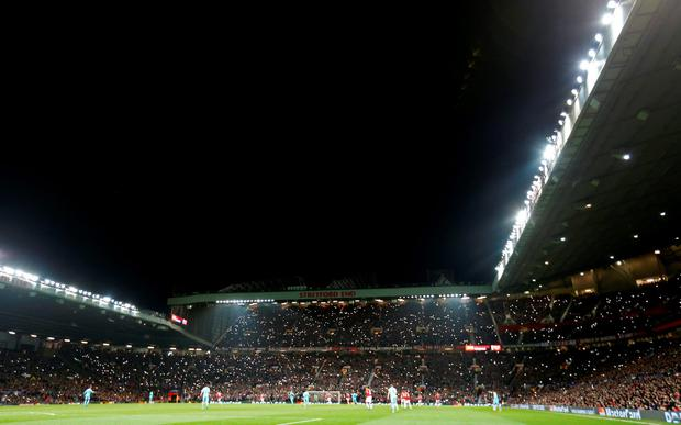 General view as Manchester United fans wave lights during the seventh minute of the match in honour of former player George Best