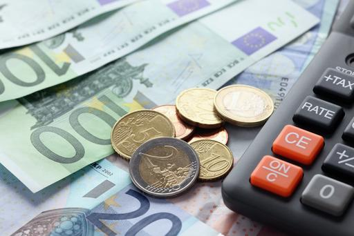 Calculator with Euro notes and coins. Finance concept. Close-up.