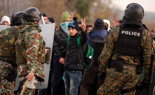 A migrant displaced by the war in Syria gestures in front of Macedonian police officers near Gevgelija, Macedonia, after trying to cross the border from Greece yesterday