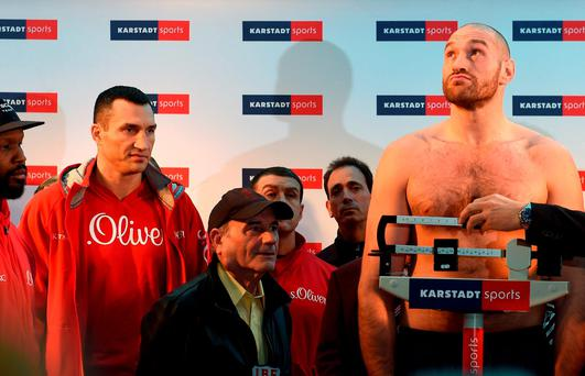 Wladimir Klitschko looks on as his challenger Tyson Fury stands on the scales during their official weigh-in in Essen