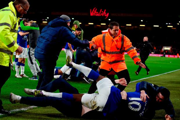 Everton supporters invade into the pitch to celeberate their team's third goal