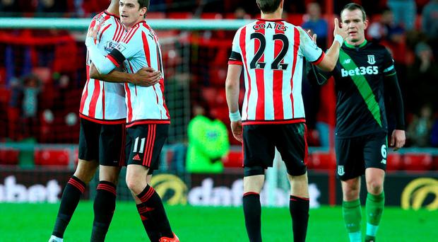 Adam Johnson of Sunderland celebrates with Younes Kaboul at the end of the game after Sunderlands 2-0 victory over Stoke during the Barclays Premier League match between Sunderland AFC and Stoke City FC at the Stadium of Light on November 28, 2015 in Sunderland, United Kingdom. (Photo by Mark Runnacles/Getty Images)
