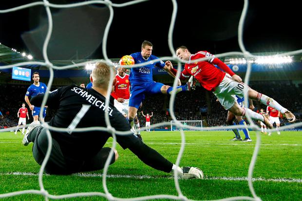 Manchester United's Wayne Rooney and Leicester's Robert Huth in action as Kasper Schmeichel looks on