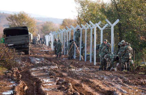 Ring of steel: Macedonian soldiers build up a metal fence at the Greek-Macedonian border near the Greek village of Idomeni