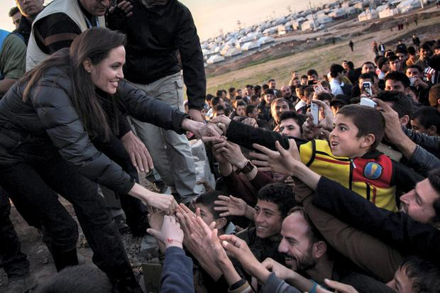 Reaching out: Hollywood star Angelina Jolie greets refugees in a camp in Northern Iraq in January