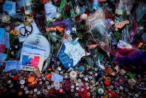 Not forgotten: Mourners set emotional tributes in front of the Bataclan concert hall in Paris last week