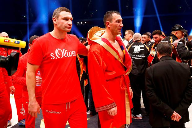 Wladimir Klitschko looks dejected after losing the fight while brother Vitaly looks on Reuters / Kai Pfaffenbach Livepic