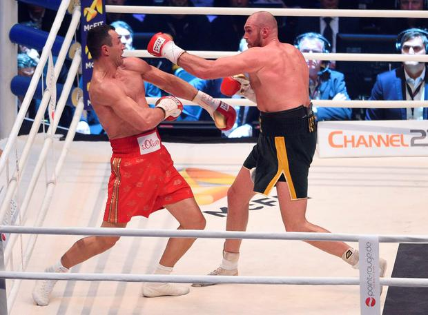 Ukraine's Wladimir Klitschko, left, and Britain's Tyson Fury exchange blows in a world heavyweight title fight for Klitschko's WBA, IBF, WBO and IBO belts in the Esprit Arena in Duesseldorf