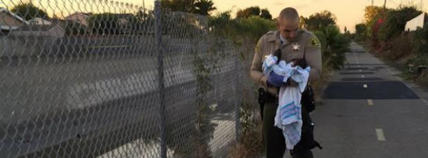 A police officer holds the newborn baby girl found in LA Credit: Facebook/LA County Sheriff Department