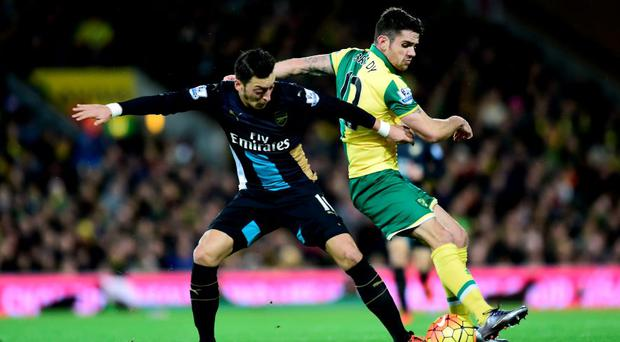 Arsenal's Mesut Ozil and Norwich City's Robbie Brady battle for the ball during the Barclays Premier League match at Carrow Road