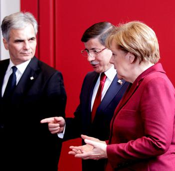 Turkish Prime Minister Ahmet Davutoglu, center, speaks with German Chancellor Angela Merkel, right, and Austrian Chancellor Werner Faymann prior to a group photo at an EU-Turkey summit at the EU Council building in Brussels on Sunday, Nov. 29, 2015. (AP Photo/Francois Walscaerts)