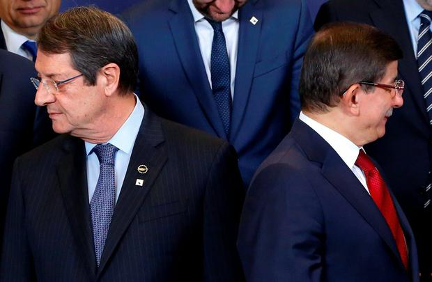 Cyprus President Nicos Anastasiades (L) and Turkish Prime Minister Ahmet Davutoglu take part in a group photo at an EU-Turkey summit, in which the EU seeks Turkish help to slow the influx of migrants into southeastern Europe, in Brussels, Belgium November 29, 2015. REUTERS/Yves Herman
