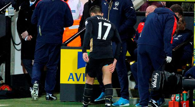 Arsenal's Chilean striker Alexis Sanchez limps off the pitch holding his leg during the English Premier League football match between Norwich City and Arsenal at Carrow Road in Norwich, eastern England on November 29, 2015. LINDSEY PARNABY/AFP/Getty Images