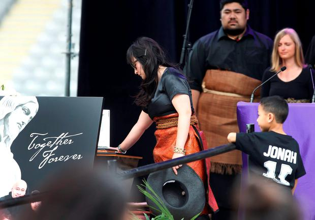 Former All Black Jonah Lomu's widow Nadene Lomu touches his casket with her son Dhyreille Lomu during his memorial service in Eden Park in Auckland, New Zealand, November 30, 2015