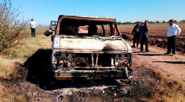 In this Nov. 21, 2015 photo, Mexican authorities inspect a burnt out van suspected to belong to a couple of Australian tourists missing for more than a week, in Sinaloa, Mexico