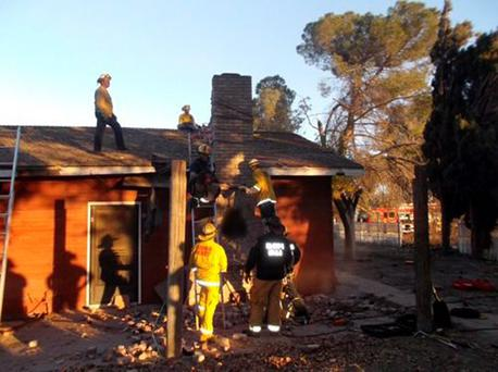 Local fire and sheriff personnel respond to a home after a suspected burglar got stuck in the chimney and died in Fresno, California November 29, 2015. A suspected burglar who attempted to enter a California home through the chimney died on Saturday after the homeowner lit a fire without realizing anyone was inside, police said