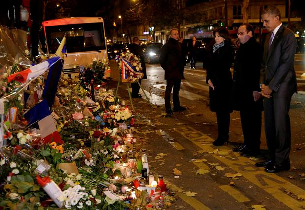 U.S. President Barack Obama, right, French President Francois Hollande and Paris Mayor Anne Hidalgo pay their respect at the Bataclan concert hall, one of the recent deadly Paris attack sites, after Obama arrived in the French capital to attend the World Climate Change Conference 2015 (COP21), Monday, Nov. 30, 2015. (Philippe Wojazer, Pool via AP)