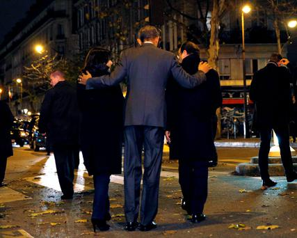 U.S. President Barack Obama, French President Francois Hollande (R) and Paris Mayor Anne Hidalgo (L) walk away after placing flowers at a makeshift memorial to pay tribute to the victims of the Paris attacks at the Bataclan in Paris November 30, 2015