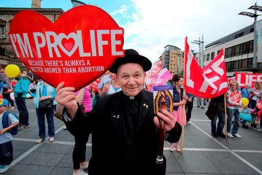 A priest attends an anti-abortion rally at Custom House Square in Belfast during the summer