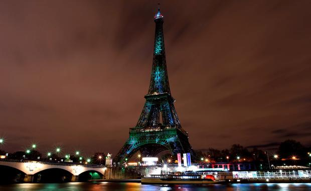 The Eiffel Tower lit up with green color and messages to prevent global warming during the first day of the United Nations climate conference in Paris