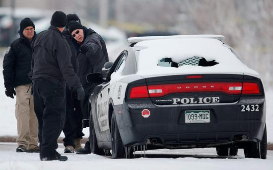 Crime scene investigators look over a police vehicle damaged during Friday's shooting spree near a Planned Parenthood clinic in northwest Colorado Springs. (AP Photo/David Zalubowski)