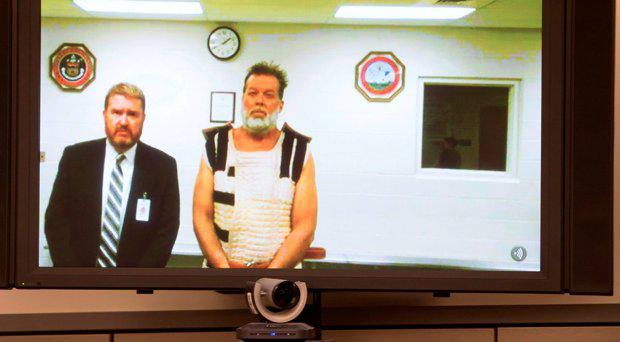 Colorado Springs Planned Parenthood shooting suspect Robert Dear, right, appears via video hearing during his first court appearance, where he was told he faces first degree murder charges, Monday, Nov. 30, 2015, in Colorado Springs, Colo. At left is public defender Dan King