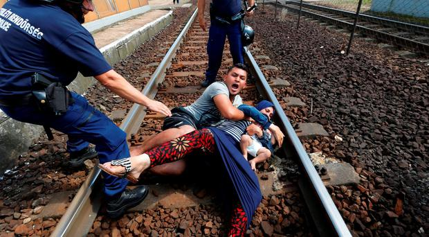Hungarian policemen stand by the family of migrants as they want to run away at the railway station in the town of Bicske, Hungary, September 3, 2015. REUTERS/Laszlo Balogh