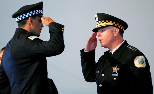 Chicago Police Superintendent Garry McCarthy (R) returns a salute to an unnamed recruit during a recruitment graduation ceremony in Chicago, Illinois on April 21, 2014.