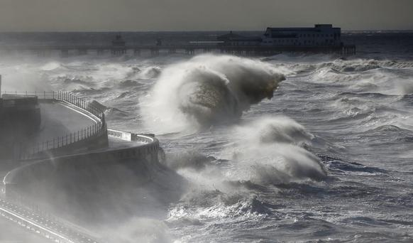 Waves break in front of the South Pier on Blackpool Promenade