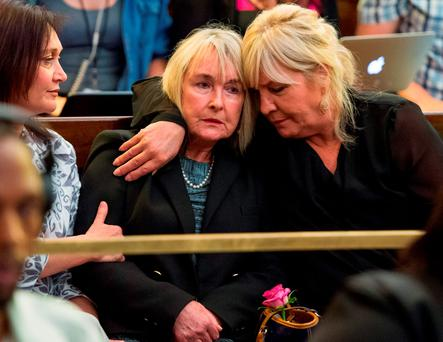 June Steenkamp, centre, the mother of Reeve Steenkamp, is comforted as appeals court judge Eric Leach delivers his verdict, during the appeals court hearing