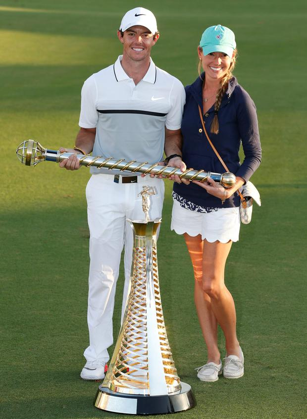 Rory McIlroy celebrates with his girlfriend Erica Stoll and trophies after winning The Race to Dubai and DP World Tour Championship. Photo: Reuters / Paul Childs