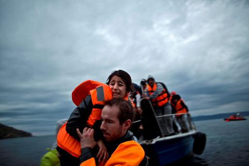 A young refugee girl is carried by a volunteer off a vessel Muhammed Muheisen (AP)