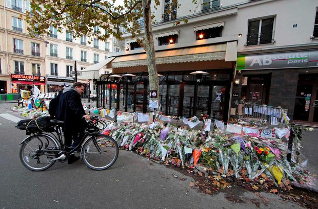 A man pauses with his bicycle near flowers in front of La Bonne Bierre Credit: Eric Gaillard (REUTERS)