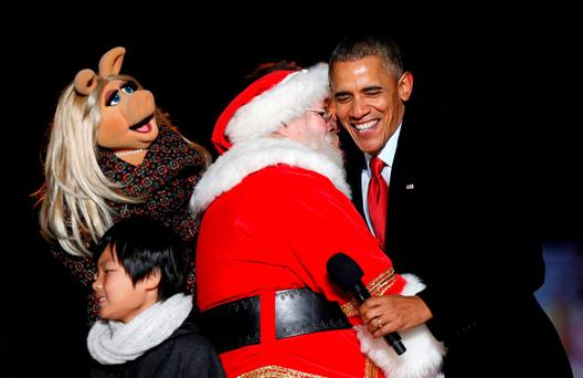 Obama, who has come under attack from EU Agriculture Commissioner Phil Hogan, hugs Santa Claus as Miss Piggy watches during the National Christmas Tree Lighting in Washington