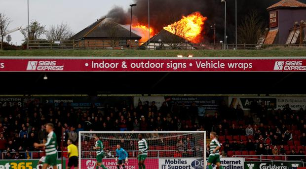 Fire rages at the near by Sixfields Tavern as play continues during the FA Cup second round match at Sixfields Stadium, Northampton. PRESS ASSOCIATION Photo. Picture date: Saturday December 5, 2015. See PA story SOCCER Northampton. Photo credit should read: Paul Harding/PA Wire. RESTRICTIONS: EDITORIAL USE ONLY No use with unauthorised audio, video, data, fixture lists, club/league logos or